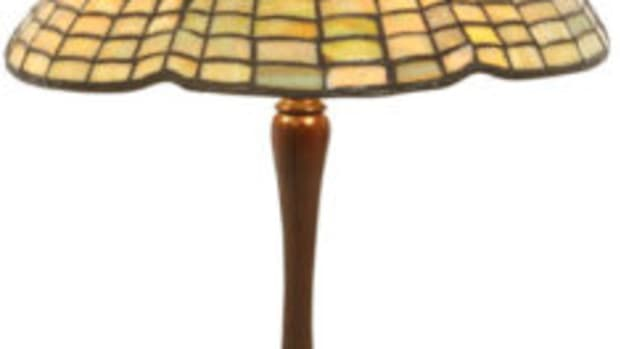 Lighting up the sale is this 15-inch Tiffany Studios Spider table lamp ($15/20,000) having a shade in golden mottled glass in the form of a domical spider web with a stylized six-legged spider running down from the top the shade.