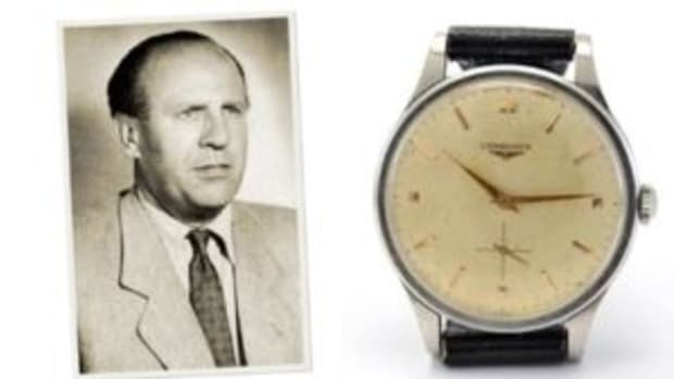 Longines wristwatch belonging to Oskar Schindler, featuring a white face with gold-tone hands and time markers, silver-tone case, and black leather strap.