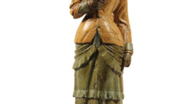 Carved ship's figurehead in the form of a woman in fancy coat with feathered hat, circa 1880, $11,500.