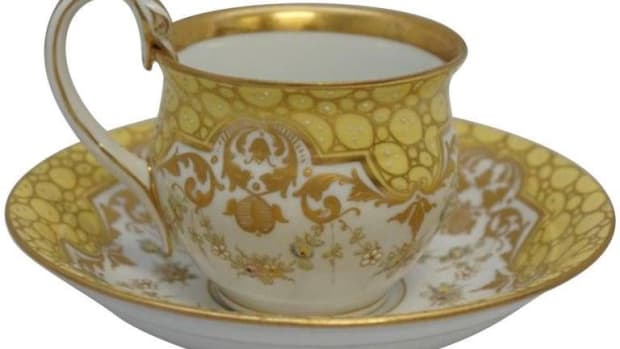 "Meissen swan-handle teacup and saucer set, heavy enameled floral swags and accents with heavy gilt, cup is 3"" d x 2-1/2"" h; saucer is 5-1/2"" d x 1-1/4"" h, $700."