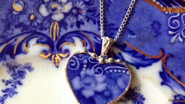 A heart-shaped pendant from a piece of flow blue pottery.