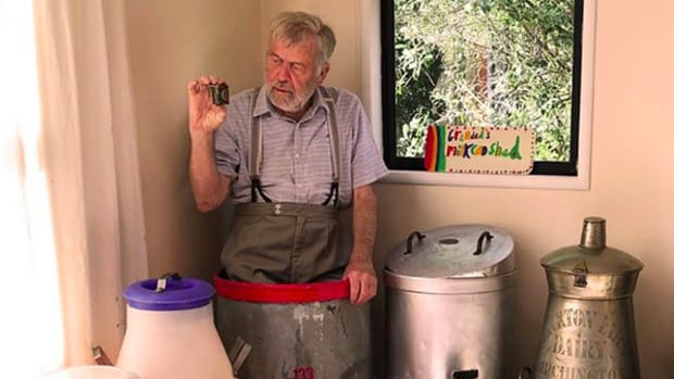 Ian Spellerberg is standing in his largest milk can (25 gallons) from New Zealand and is holding the smallest milk can in the world (1/8th of a pint) from England. His adopted cat Florence (found as a kitten on a country road) watches with interest. Also shown are three modern plastic milk cans on the left. On the right there are two unusual cans with spouts.