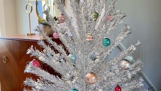 An Evergleam 94-branch stainless aluminum six-foot Christmas tree with tripod stand, 1960s, by Aluminum Specialty of Manitowoc, Wisconsin. The Shiny Brite ornaments shown on tree were not included with the sale; $500.