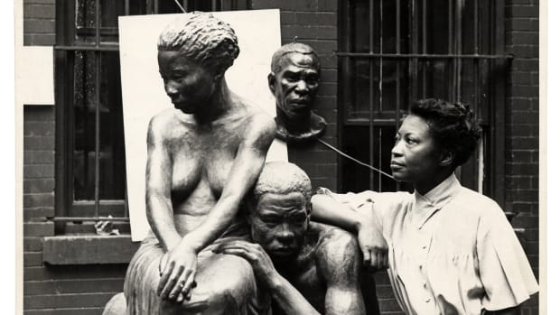 Augusta Savage posing with her sculpture Realization, created as part of the Works Progress Administration's Federal Art Project, circa 1938.