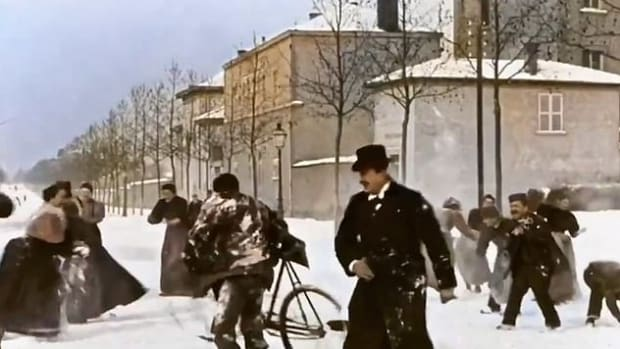 A dapper gentleman, snow-covered cyclist, and at far left, a woman in a bustle packing a snowball.