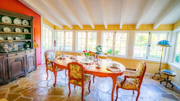 A vintage carved oval dining table with four armchairs featuring bird and foliate embroidered upholstery highlights a sunny room in Doris Day's home. Day was known to personally refinish her furnishings. Many items feature this reddish orange color.