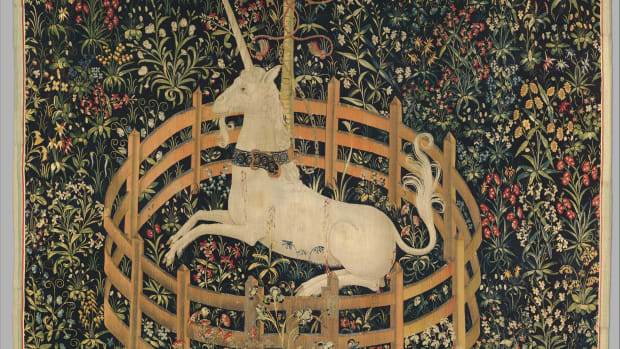 "Tapestry 7: The Unicorn in Captivity. This tapestry shows the unicorn alive and well, and entirely tamed. He is fenced in and chained to a tree, but the chain is less than secure and the fence is low enough to leap over. He has submitted to his captivity. The red stains on his flank, according to the Met, ""do not appear to be blood, as there are no visible wounds like those in the hunting series; rather, they represent juice dripping from bursting pomegranates"" — a medieval symbol of marriage and fertility. Many of the other plants represented here, such as wild orchid and thistle, echo this theme of marriage and procreation: they were acclaimed in the Middle Ages as fertility aids for both men and women."