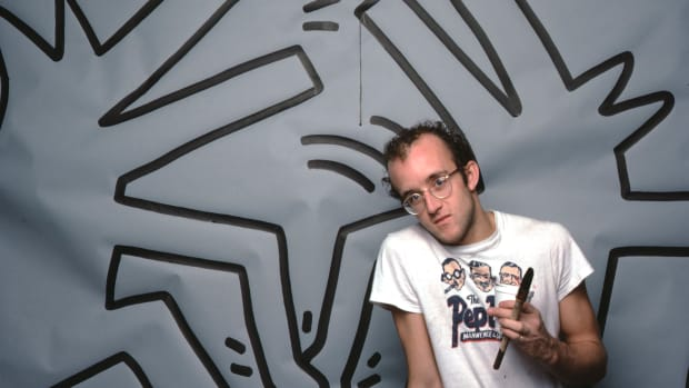 Artist Keith Haring with one of his paintings in April 1984.