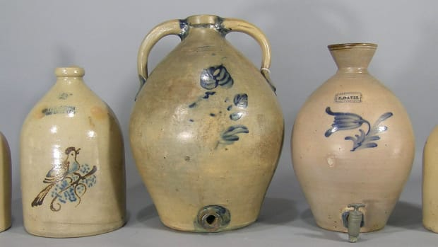 "Various stoneware jugs are up for bid, including the rare 19th century Julius Norton cobalt-decorated stoneware jug shown in the middle; ovoid, Bennington, VT, 5-gallon, two handled, having a cobalt flower decoration on the front and cobalt decoration at each end of the handles, 17-3/4"" h; estimate: $3,000-$5,000."