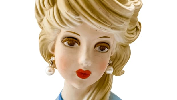 """Elusive Inarco E-6210 head vase dubbed the """"Ghost Girl"""" or """"Ghost Sister"""" by collectors because of her light matte coloring and is a scarce find. Circa 1950s-60s, she has a medium-blue bodice with a deeper blue narrow collar topping a peek-a-boo V in the front of her gown, large pearl drop earrings, side-swept blonde hair, mark reads """"Inarco® E6210"""" with an elliptical world map, 7"""" h, base is 4-1/4"""" x 2-3/4""""; $275."""