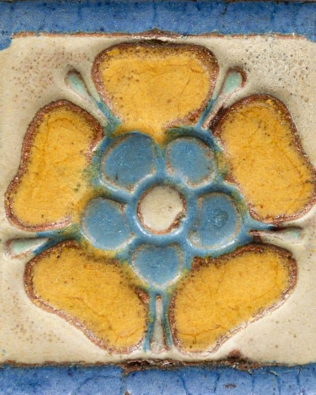 A Grueby art pottery tile of a Tudor rose.