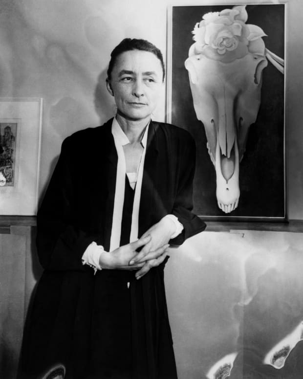 "Georgia O'Keeffe next to her painting Horse Skull with White Rose at an exhibit of her work titled ""Life and Death."""