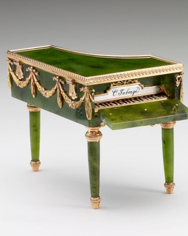 """This miniature grand piano in Louis XVI style was made by Mikhail Perkhin. It's made of nephrite with mounts of red and green gold, and the keyboard is opaque black and white enamel. Foliate swag mounts are around the edge and the top is hinged; 2"""" x 2.8"""" x 2"""". Judging by her acquisitions, Queen Mary was particularly fond of Fabergé's miniature objets de fantasie, which include several examples of miniature furniture in the form of bonbonnières. These objects afforded the craftsman the opportunity to demonstrate skill in applying specialist techniques to replicate the real materials of the full-scale object. This miniature piano of Siberian nephrite is carved and polished to resemble ebonized wood. The lid opens for use as a bonbonnière and the front drops down to reveal the keyboard in gold and enamel, inscribed """"C. Fabergé."""" The piano belonged originally to Tsarina Alexandra Feodorovna and is also seen in one of the display cases in photographs of the exhibition of Fabergé held in St. Petersburg in 1902. Queen Mary acquired it sometime between 1922-1931."""