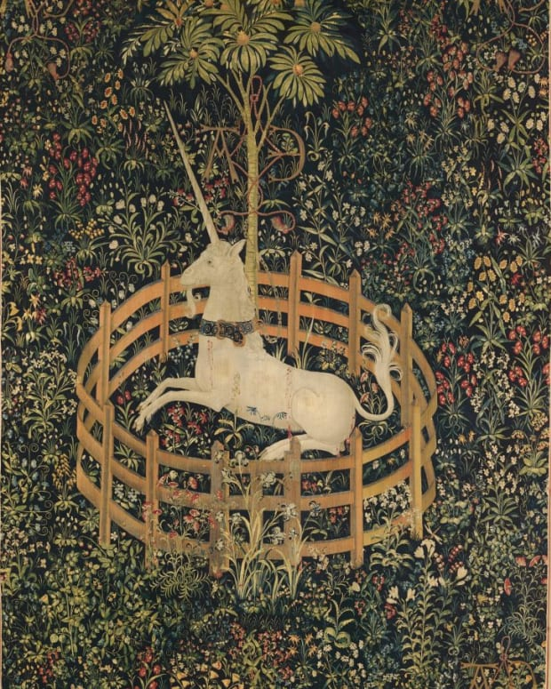 """Tapestry 7: The Unicorn in Captivity. This tapestry shows the unicorn alive and well, and entirely tamed. He is fenced in and chained to a tree, but the chain is less than secure and the fence is low enough to leap over. He has submitted to his captivity. The red stains on his flank, according to the Met, """"do not appear to be blood, as there are no visible wounds like those in the hunting series; rather, they represent juice dripping from bursting pomegranates"""" — a medieval symbol of marriage and fertility. Many of the other plants represented here, such as wild orchid and thistle, echo this theme of marriage and procreation: they were acclaimed in the Middle Ages as fertility aids for both men and women."""