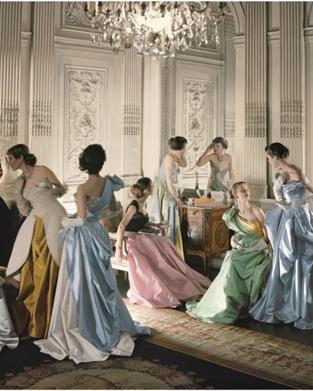 A famous Cecil Beaton photo from 1948 of nine models, including Marilyn Ambrose, Dorry Adkins, Carmen Dell'Orefice, Andrea Johnson, Lily Carlson, and Dorian Leigh, wearing various gowns by Charles James while posing in French & Company's eighteenth century French paneled room.