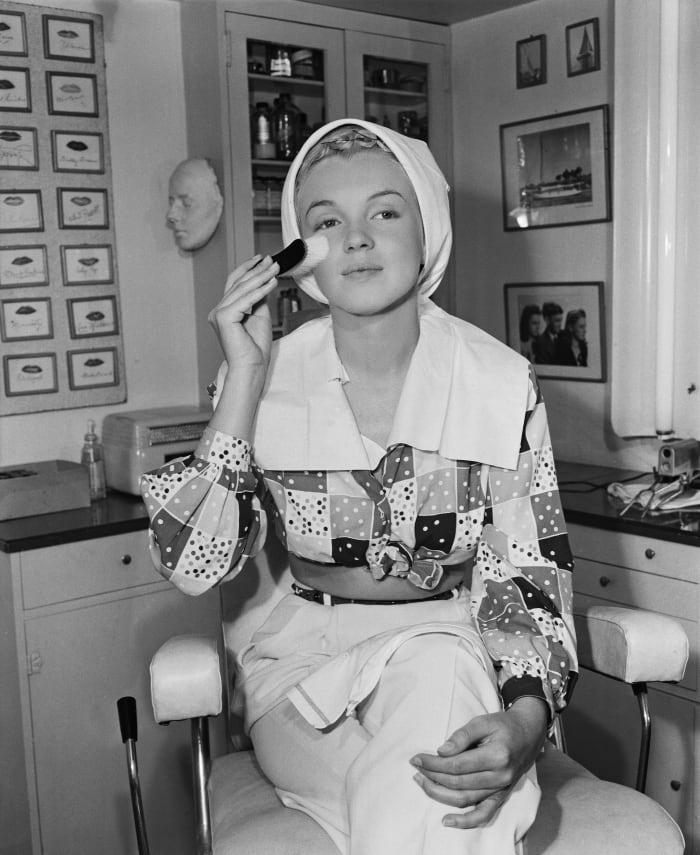 Marilyn Monroe begins her skin-care routine before applying her makeup.