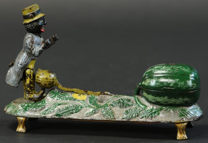 Only a handful of examples are known to exist of this bank by J&E Stevens Co., circa 1888, which brought a winning bid of $80,000. A very desirable pedestal-styled bank and the rarest, it is a marvel in casting effects and its action which involves a figure aggressively kicking a small watermelon into larger one for the coin deposit.