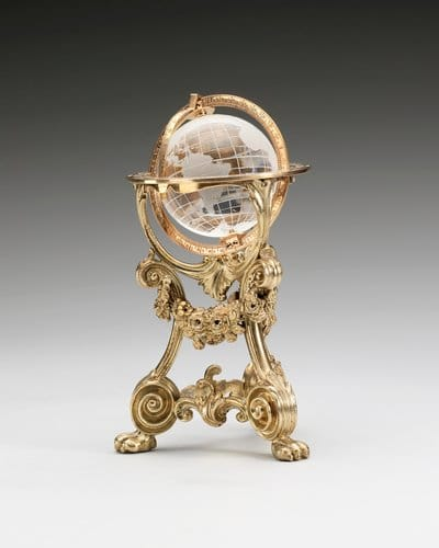 """This rock crystal, gold and silver-gilt globe was made sometime before 1896 in the workshop of Erik Kollin, Carl Fabergé's first head workmaster. It was purchased by Tsar Nicholas II in December 1897 for 350 roubles and was subsequently owned by Prince Vladimir Galitzine, from whom Queen Mary purchased it in December 1928. The globe is geographically correct and swivels within its mounts; 4"""" x 2-1/2""""."""