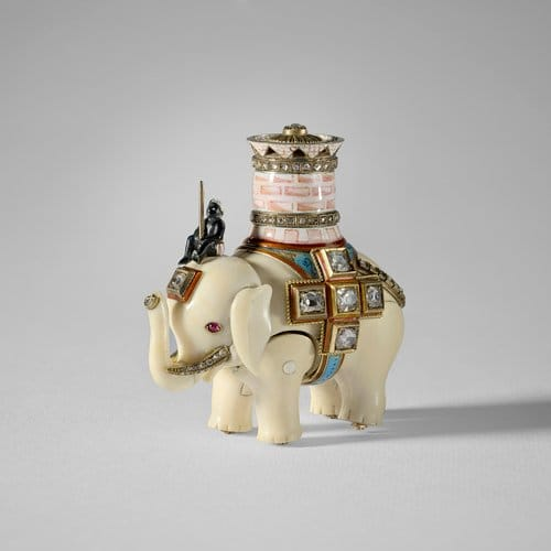 """Mikhail Perkhin made this ivory elephant automaton in 1892; 2-1/2"""" x 2"""" x 1-1/2"""". The elephant has separate, jointed body legs and head and is ridden by an enamel man sitting on its head and carrying a pink and white enamel castle with two rose-cut diamond set bands and a pierced upper rim; the top set with a single diamond in gold. This automaton was made as the """"surprise"""" for the Diamond Trellis Egg, made by Carl Fabergé for Tsar Alexander III. The Tsar presented the egg to his wife, Tsarina Maria Feodorovna, for Easter 1892. The elephant is wound with a watch key through a hole hidden underneath the diamond cross on one side of the elephant. It walks on ratcheted wheels and lifts its head up and down. You can learn more and watch a short video about this piece here."""