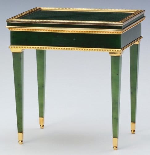 """Rectangular miniature Louis XVI-style table by workmaster Mikhail Perkhin, 1896-1903, is made of nephrite and mounted with red gold borders and has tapering legs with gold feet and a chased lid with leaves around edge and is hinged; 3"""" x 2.7"""" x 2"""". Fabergé produced a number of bibelots in the form of miniature furniture. Some, such as this table, were intended to be used as bonbonnières, fancy boxes for bonbons. This was a Christmas present for Queen Mary by Lord Revelstoke in 1921."""