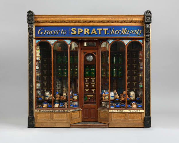 """Model of a grocery store called """"Grocer to SPRATT Her Majesty,"""" with a glazed door and windows and a display of miniature baskets, jars and bottles of food. Inside is a wooden counter and at the back of the store are wooden drawers and metal jars that contain spices and groceries. The whole model is in a glass case; 28-1/2"""" x 32"""" x 24-1/2""""."""