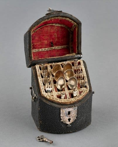 """This black rough leather box with sloping hinged lid and box front contains a set of silver miniature cutlery of six knives, six spoons and six forks, and a silver key; 3-1/2"""" x 2-1/2"""" x 2"""". This was acquired by Queen Mary."""