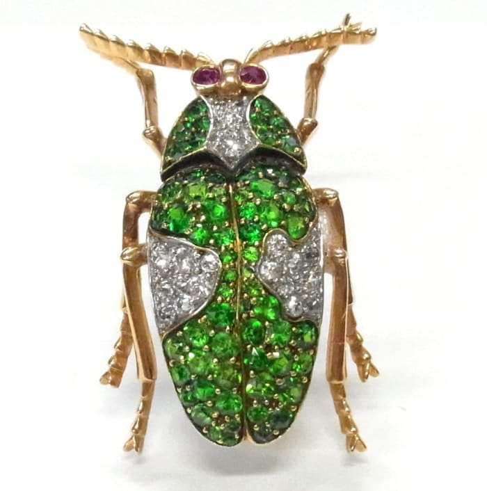 """An 18k rose gold beetle brooch, encrusted with ultra-fine green demantiod garnets and old cut diamonds, and two ruby eyes, 1-3/8"""" x 7/8""""; estimate: $3,000-$5,000."""
