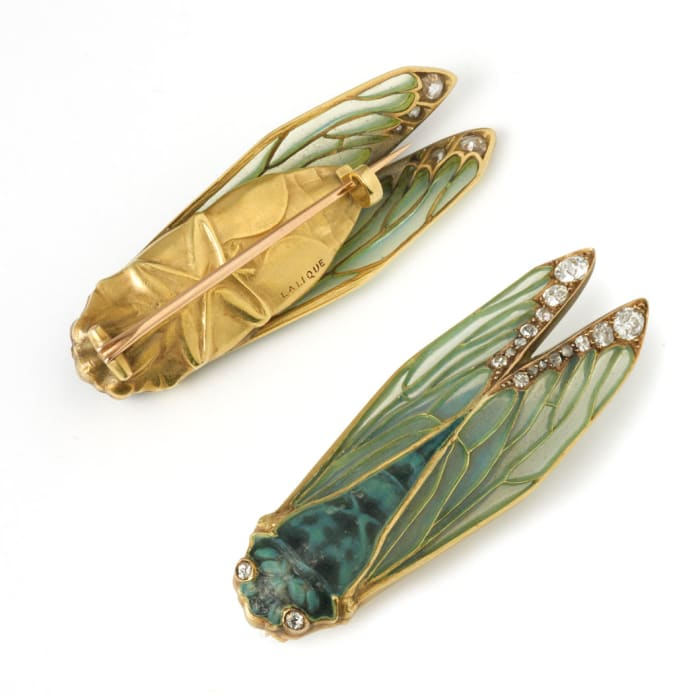 René Lalique cicada brooch, c.1905, faithfully capturing every detail of the insect. Its delicate wings decorated with translucent green plique-à-jour enamel, the tips mounted with old European-cut diamonds, the body in rich mottled blue/green glass, and the eyes set with diamonds in gold collets; the reverse is chased yellow gold.