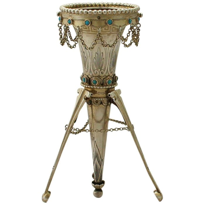 """Victorian sterling silver posy holder, 1874, conical shaped form on three legs, embellished with bright cut engraved Greek Key fret band ornamentation and stylized leaves, beads, a scalloped border and collet-set cabochon turquoise, 5"""" h; $2,883."""