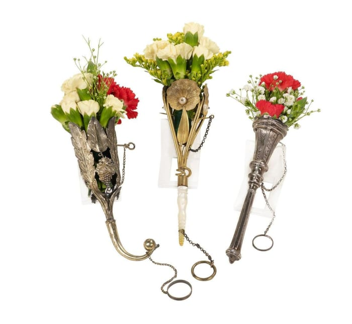 """Lot of three Victorian tussie-mussies, late 19th century, each with a chained pin and finger ring: gilt metal with embossed lily pads centered by a faux pearl, turned nacre handle, 6-1/4"""" l; silver with tapering paneled cup and handle, engraved scrolls, 5-3/4"""" l; and gilt metal with embossed acanthus fronds and grape clusters, scroll handle with ball finial, 5-1/2"""" l; $950."""