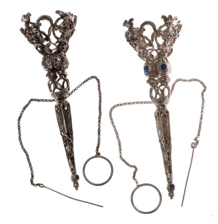"""Pair of antique .900 fine silver tussie-mussie holders with red and blue crystals and an elaborate reticulated design set with glass jewels, 5-1/4"""" h; $275."""