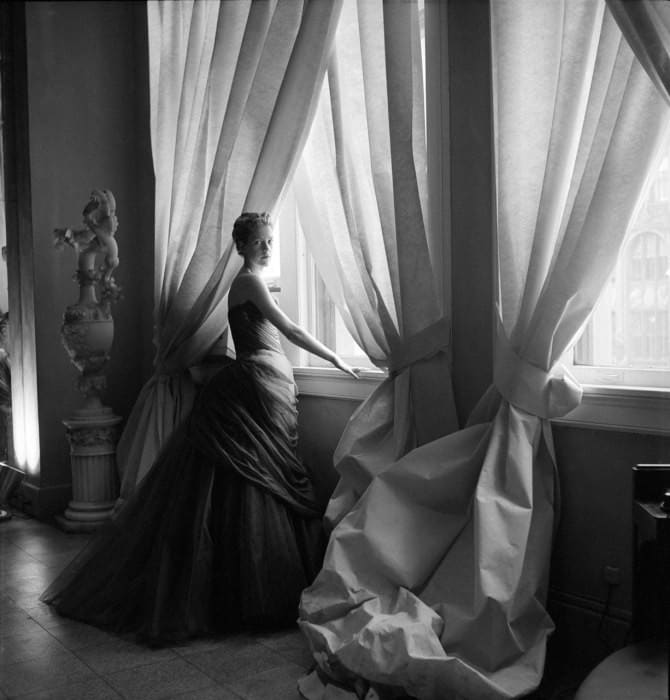 The Swan ball gown immortalized in this Cecil Beaton photograph of Charles James' wife, Nancy James, posing by light-filled Pellon-covered windows in the James' showroom.
