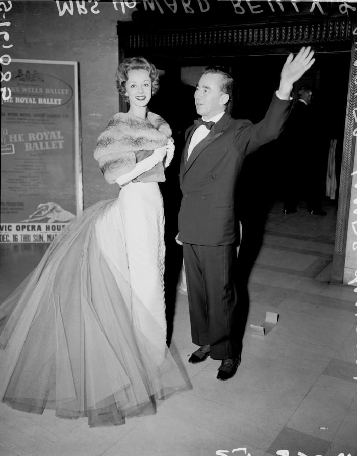 Fashion designer Charles James with one his clients, Mrs Howard Reilly, wearing one of his Butterfly gowns in 1957.