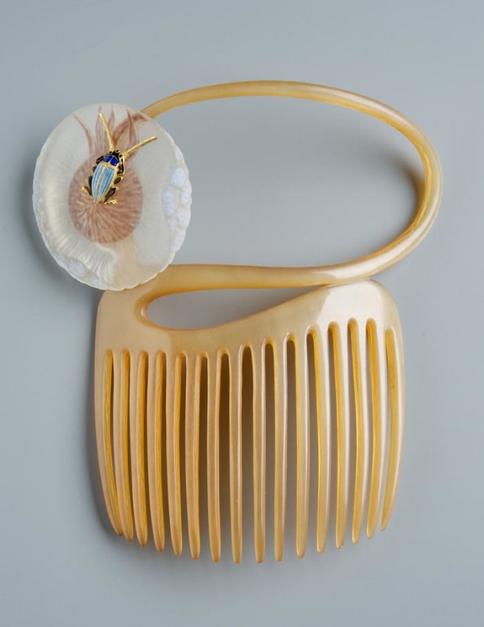 """This comb, circa 1898-1899, is sawed of a light, transparent horn. Its curved top is continued in a tendril that recoils in an upturned S-shape. The tendril ends in a round, puffy blossom of a lion's tooth made of matte-etched glass. There is an enameled, naturalistic insect sitting in the center of the flower: a golden bug with two long feelers, a blue chitin cover and black legs. The rim of the petal is of irregular thickness, being blue opaque at the wider places. This comb is also a typical example of Japanese influence of Lalique's work; 4.3"""" h, 3.9"""" w."""