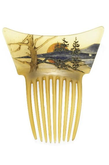 """Orange Sun Landscape: In the second half of the 20th century, the land of the rising sun was opening up to the rest of the world, and Japanese art was beginning to inspire many European artists, including Lalique. He decorated this horn comb, circa 1900, with a blue and green enameled mountain landscape and trees at sunrise. The scene is reflected in water, creating a mirror image. In the foreground, a leafless tree anchors and balances the composition; 5-1/4"""" x 4-1/2"""". This sold at Christie's in 2009 for $92,500."""