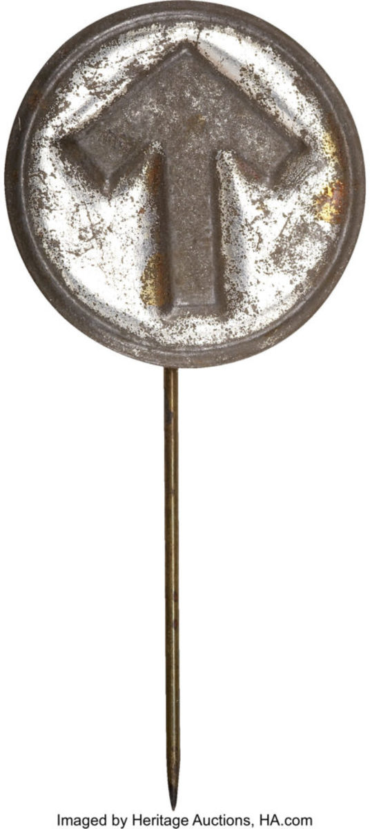 This pressed-metal stick pin is English in both manufacture and distribution. Sylvia Pankhurst, the artist-daughter of Emmeline Pankhurst, one of the founders of the W.S.P.U. (Women's Social and Political Union), designed the famous Portcullis or Holloway prison brooch which was based upon the portcullis symbol of the House of Commons. It featured a superimposed arrow in purple, green, and white, the colors of the W.S.P.U., over the Commons gates. These brooches were given only to those who went to prison for the cause, although the design did appear on tea cups and post cards sold to the public. The arrow, which represented the obstructions at the bottom of the gate, became an iconic symbol in its own right, and it appeared on several varieties of hat pin without any explanatory wording, the symbol becoming well known. One also finds this exact symbol on photographs of prison garb worn by suffragists. This is the first known example of the arrow on a stick pin. Loss to finish on the high spots, else very good. Sold for $239. Courtesy of Heritage Auctions, www.ha.com