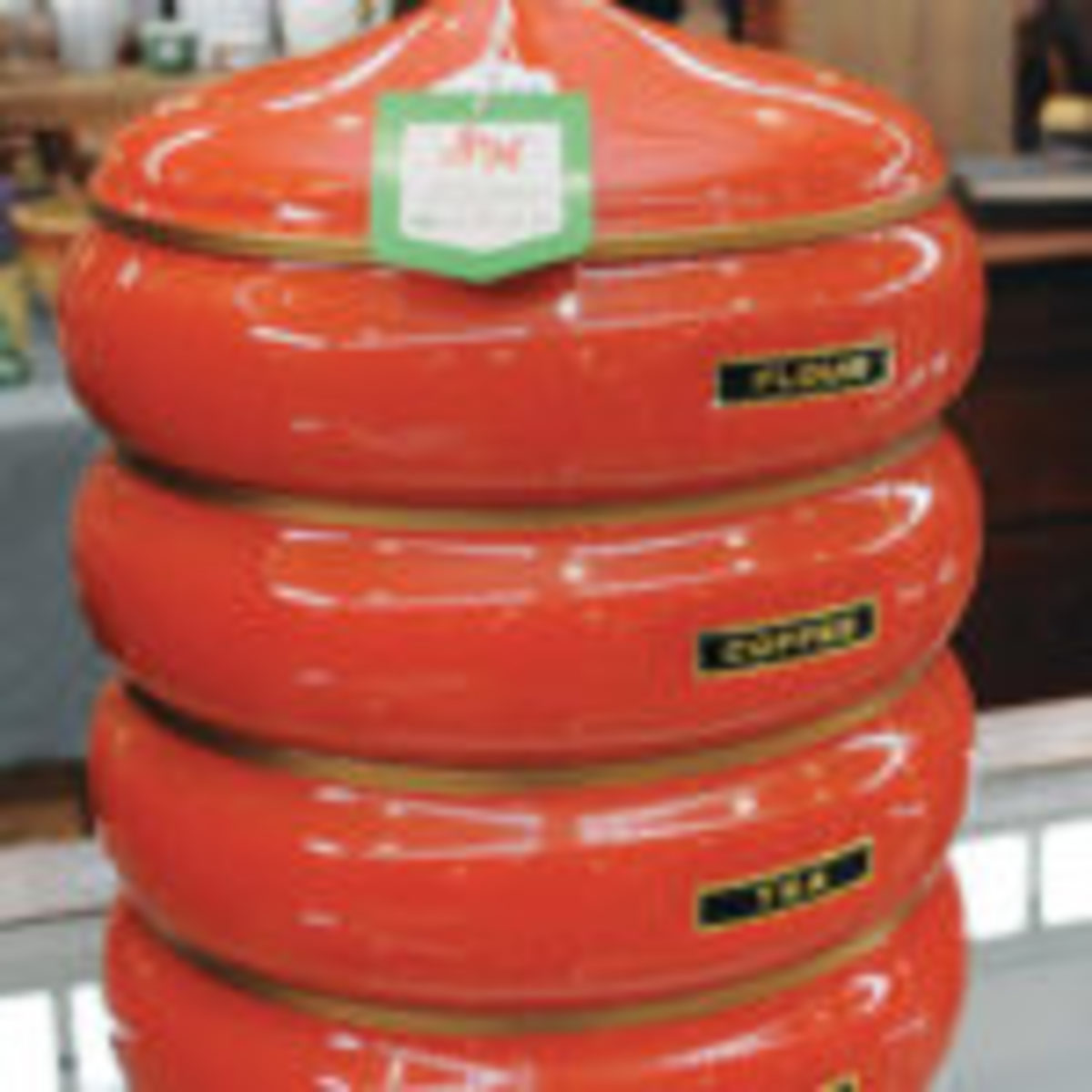 A set of vintage, orange canisters sits on display in a vendor's booth at the January Scott Antique Markets show in Columbus, Ohio.