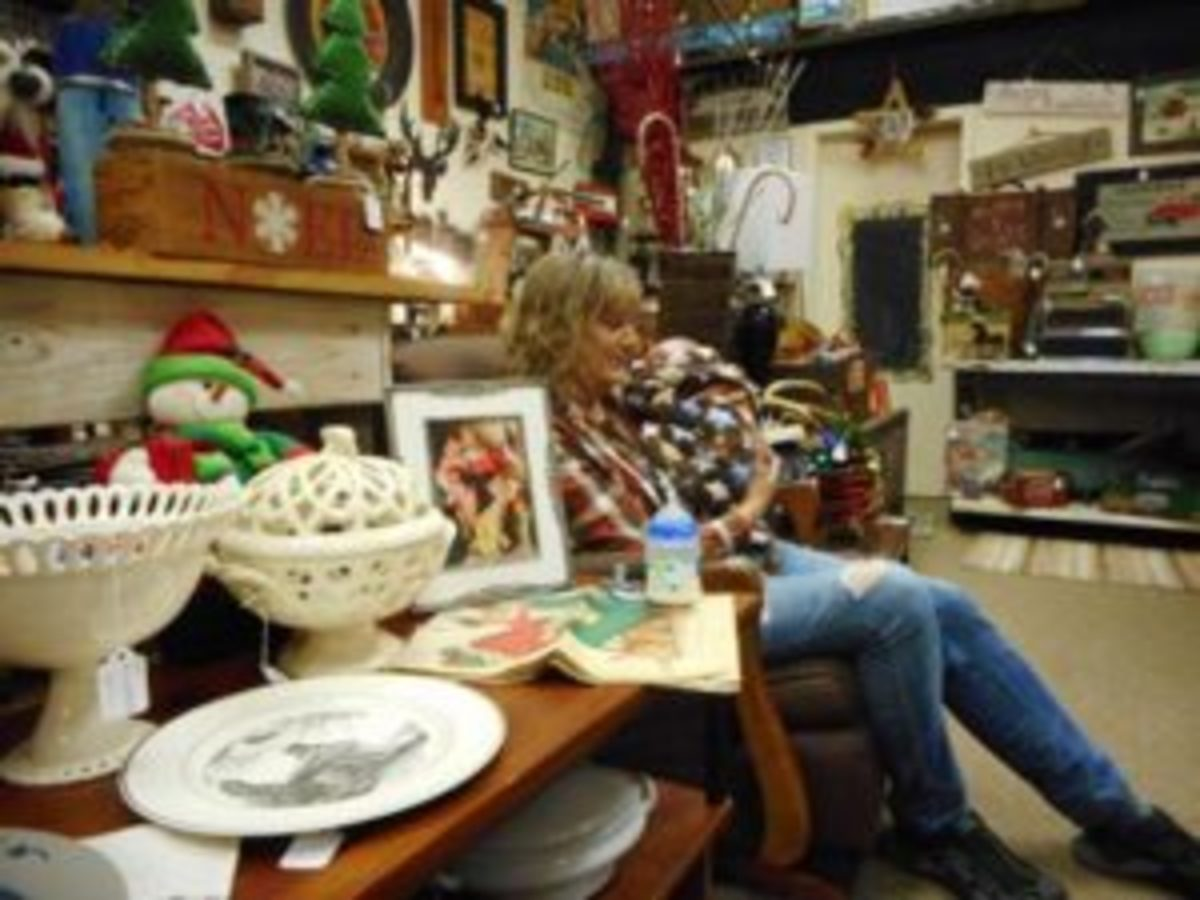 Terry Olson, owner of Time and Again Vintage in Dodgeville, Wisconsin, rocks her sister-in-law's grandchild amid the displays while they both work at the store. Photo by Mary Glindinning