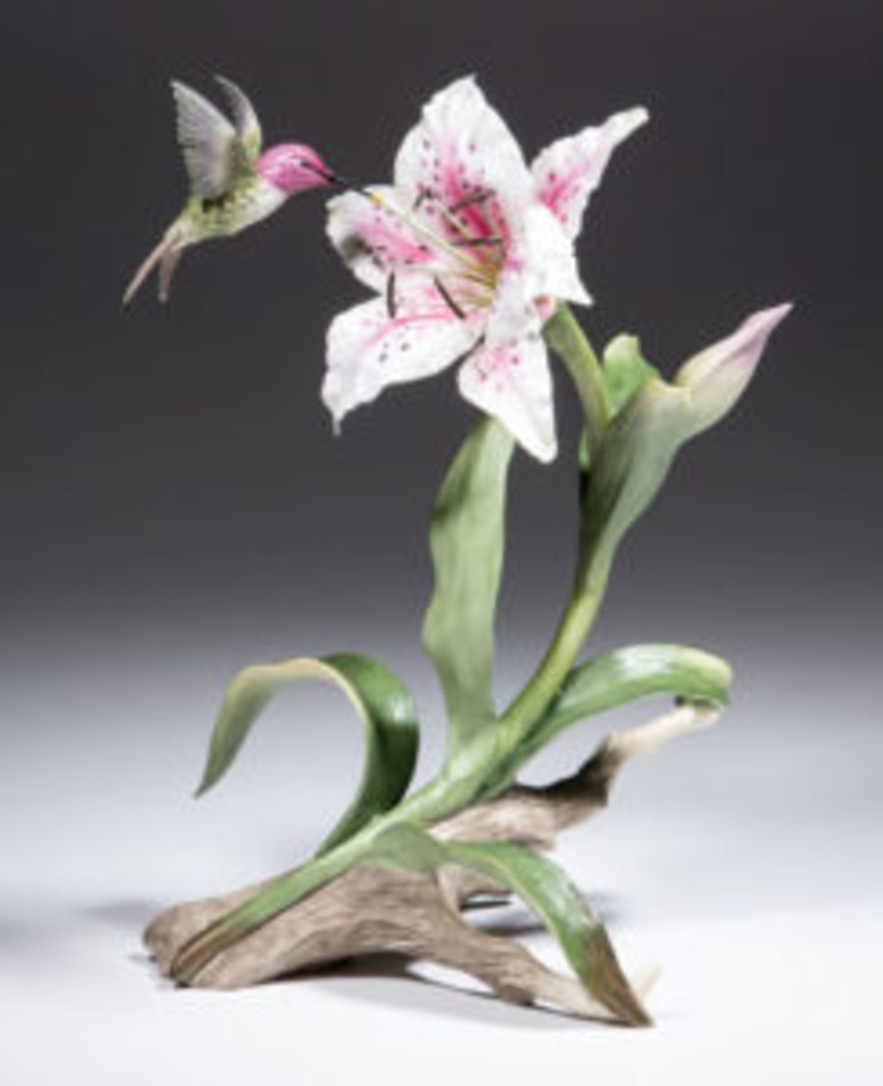 "American Boehm signed porcelain hummingbird figure. Circa 1991, 12 1/4"" tall. Brightly designed Costa's Hummingbird with Rubrum Lily, #324, perched beside an open lily on a branch with stem. Marked with black ""Boehm"" over feather beneath horse head and ""MADE IN U.S.A.,"" hand-signed by member of Boehm family. Sold through Jeffrey S. Evans & Associates, Mt. Crawford, Virginia, in October 2016 for $555.75. Image courtesy of Jeffrey S. Evans & Assoc., Inc., William McGuffin, photographer."