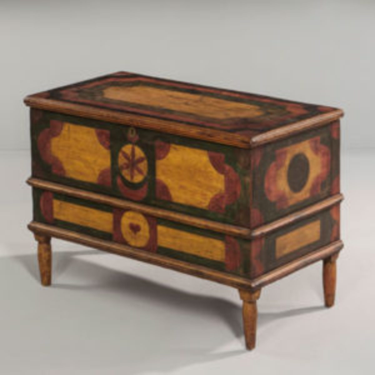 Small geometric paint-decorated blanket chest, 22 1/2 x 32 x 17 in., possibly New York or Pennsylvania, early 19th century. Applied moldings and short turned tapering legs, decorated in yellow, green, red, and black, the designs incorporating quarter-round, heart, and pinwheel elements. Courtesy of Skinner, Inc.