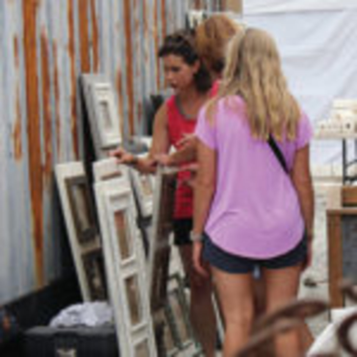 A group of customers looks through pieces in an outdoor booth at Scott Antique Markets in Atlanta.