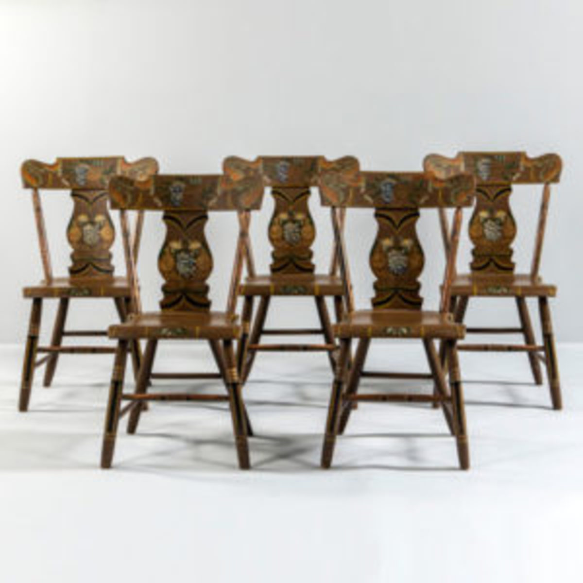 Set of five paint-decorated dining chairs, 32 3/4 x 16 3/4 in., Pennsylvania, c. 1825-35. Shaped crests above turned spindles and vasiform splats, allover light brown paint with polychrome fruits, flowers, striping and bordering. Courtesy of Skinner, Inc.