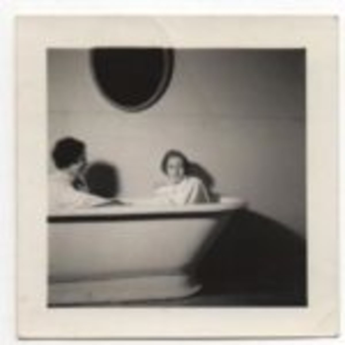 "The ""Bathtub Women"" is a simple image that isn't hard to ""read."" The absurdity of the two women, clothed and in a tub together, is formalized by the relationship between the dark oval-shaped mirror on the wall and the oval-shaped white ceramic tub and further enhanced by the wonderful shadows. That the two women are not posed for the camera together, but that one is focused on the other, while that other is focused on the photographer creates a much more interesting dynamic. And, of course, there is the question that will never be answered: ""Why are they in the robed women in the tub together?"" Courtesy Mark Glovsky Collection."