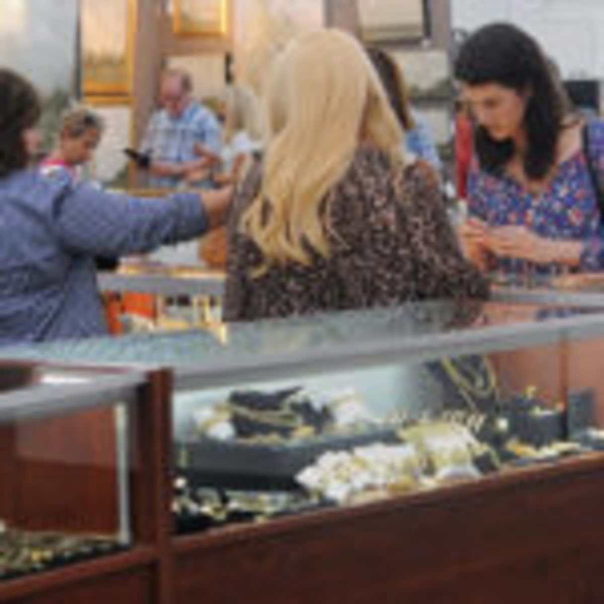 Customers looks through a jewelry case with the help of a vendor at Scott Antique Markets in Atlanta. Photos courtesy of Jess Grimm, Scott Antique Markets