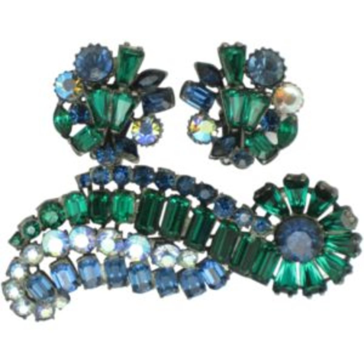 Stunning and large vintage signed Claudette emerald, sapphire, aurora borealis rhinestone and keystone brooch and matching clip style earrings. The set features a gorgeous combination of stones including emerald green keystones and baguettes, sapphire blue chatons, baguettes and navettes and aurora borealis chatons. $94. Courtesy of Ruby Lane