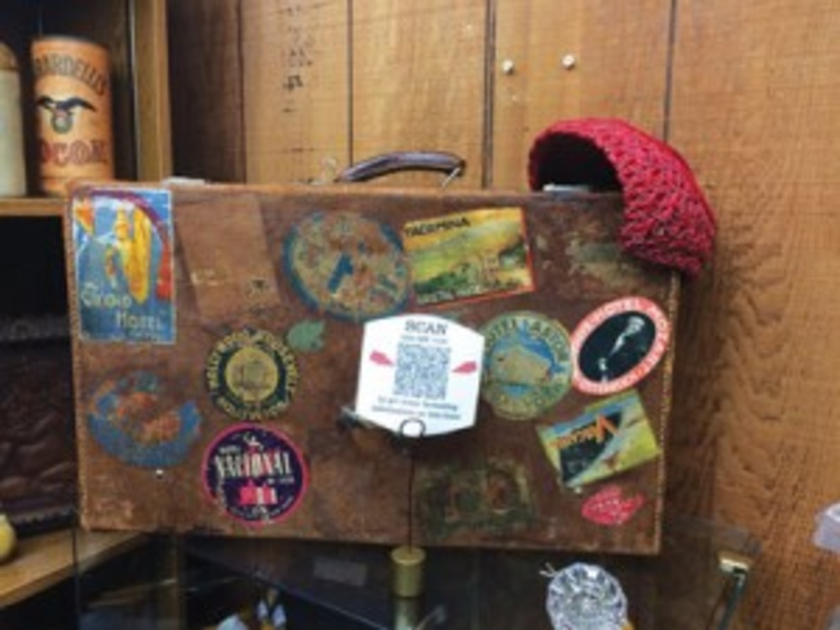 Above, the history and the character of pieces, like this circa 1930 Migato suitcase, are easily shared with the use of QR codes – shown in front of the suitcase. Photo courtesy Nostalgia Palace