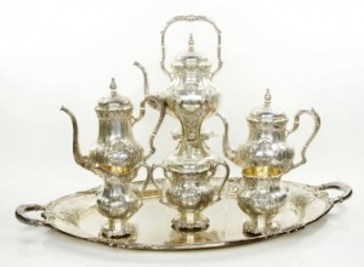 "International Sterling tea set, seven pieces, in the hand chased ""Richelieu"" pattern, to include: 12"" h coffee pot, 10 1/2"" h tea pot, 15 1/2"" h hot water kettle on stand, 8"" h covered sugar, 6 1/4"" h creamer, 5 1/2"" h waste bowl, 32 1/2"" x 20"" tray, approximtely 393 troy oz TW, and it may command $10,000 to $15,000."