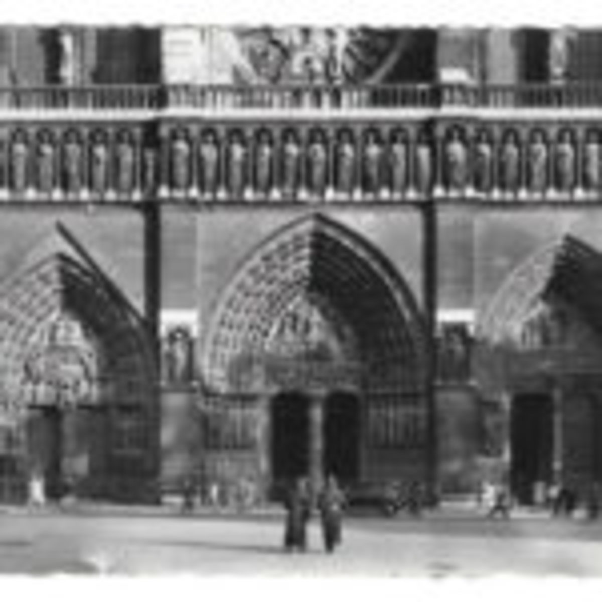 Glossy Yvon realphoto postcard with deckled edges showing portals on the west façade of Notre-Dame de Paris.