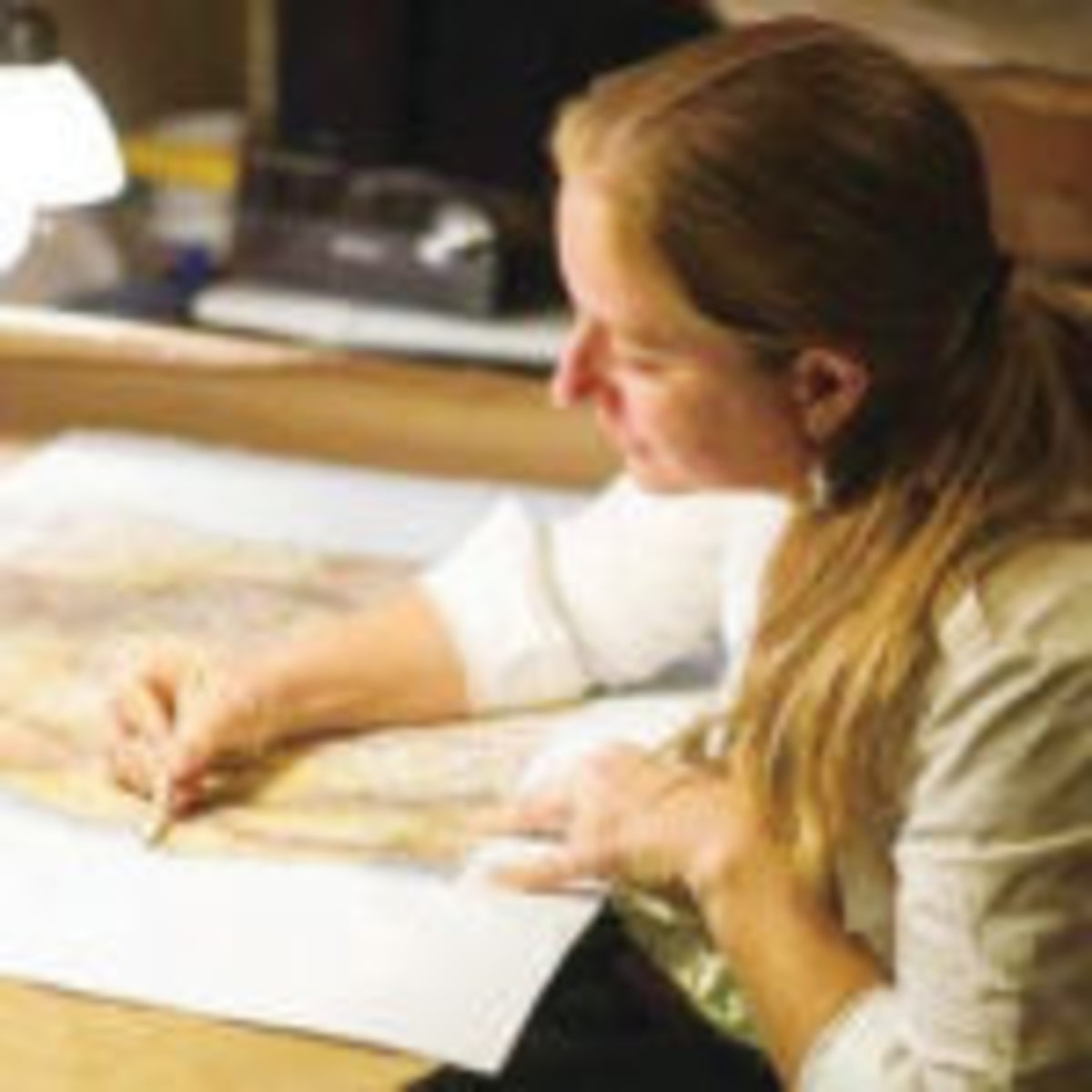 Lisa Middleton, owner of Great River Arts, at work on a map.