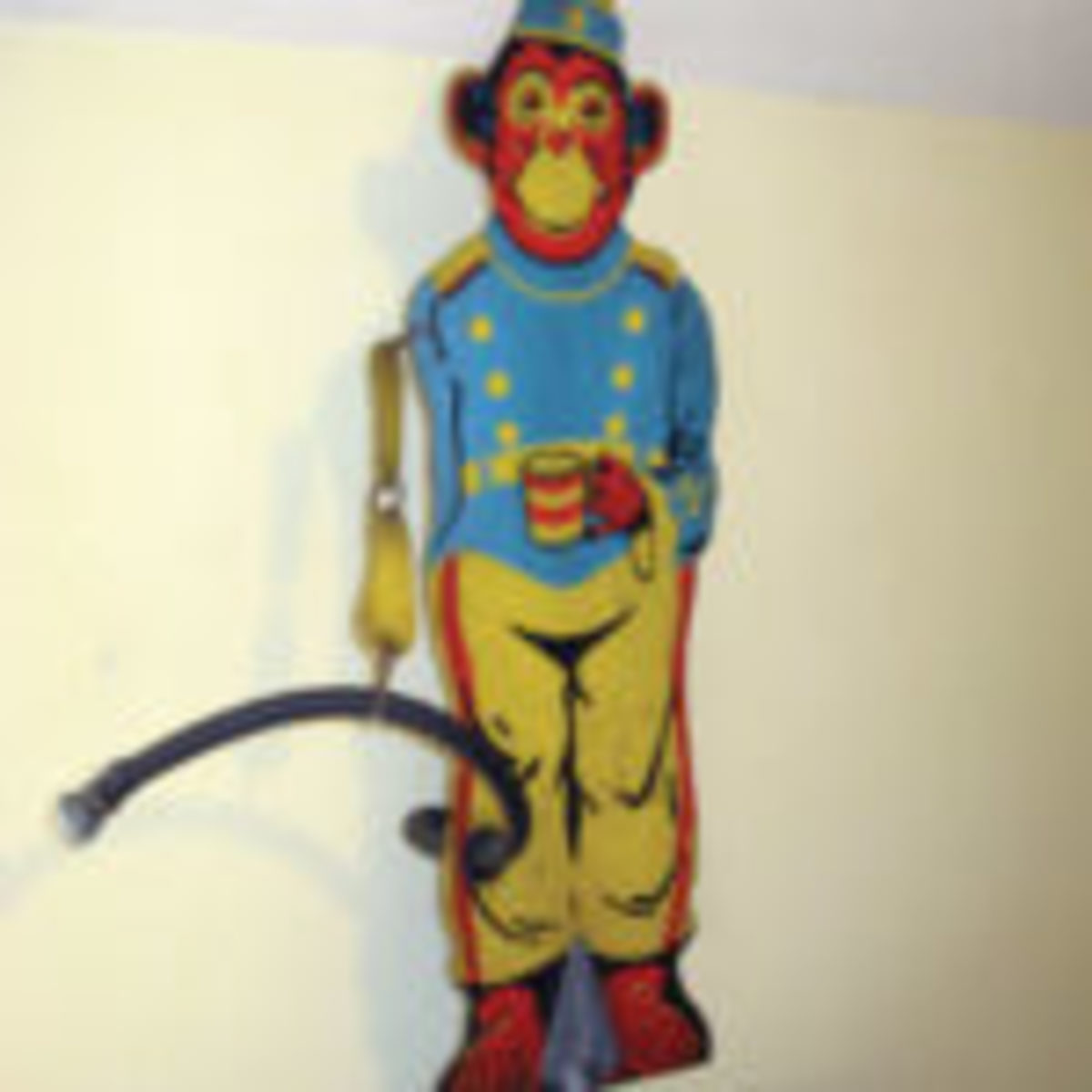 Vintage monkey figural sprinkler; stamped painted metal. Monkey holds black tail, functioning as a hose; as monkey spins water sprays from the hose. Manufacturer unknown. $165. From the author's collection.